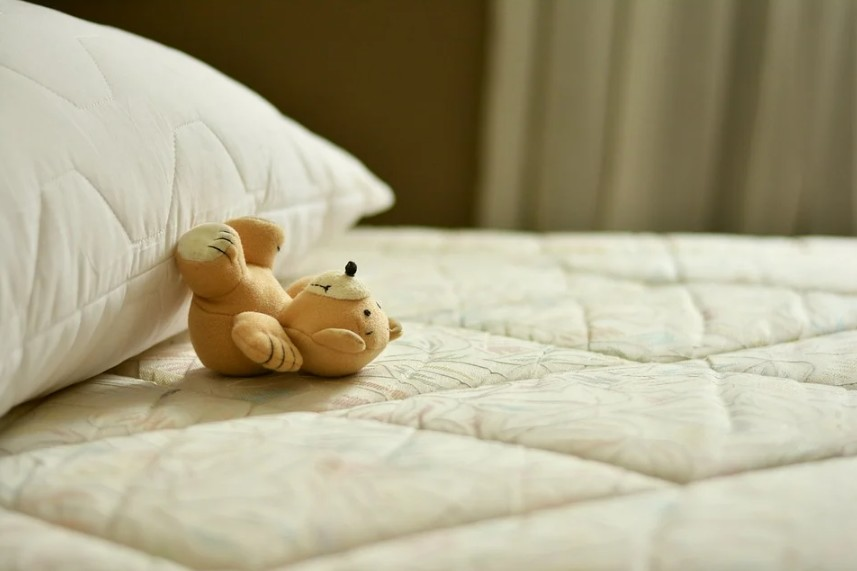 mattress with a teddy bear on top of it